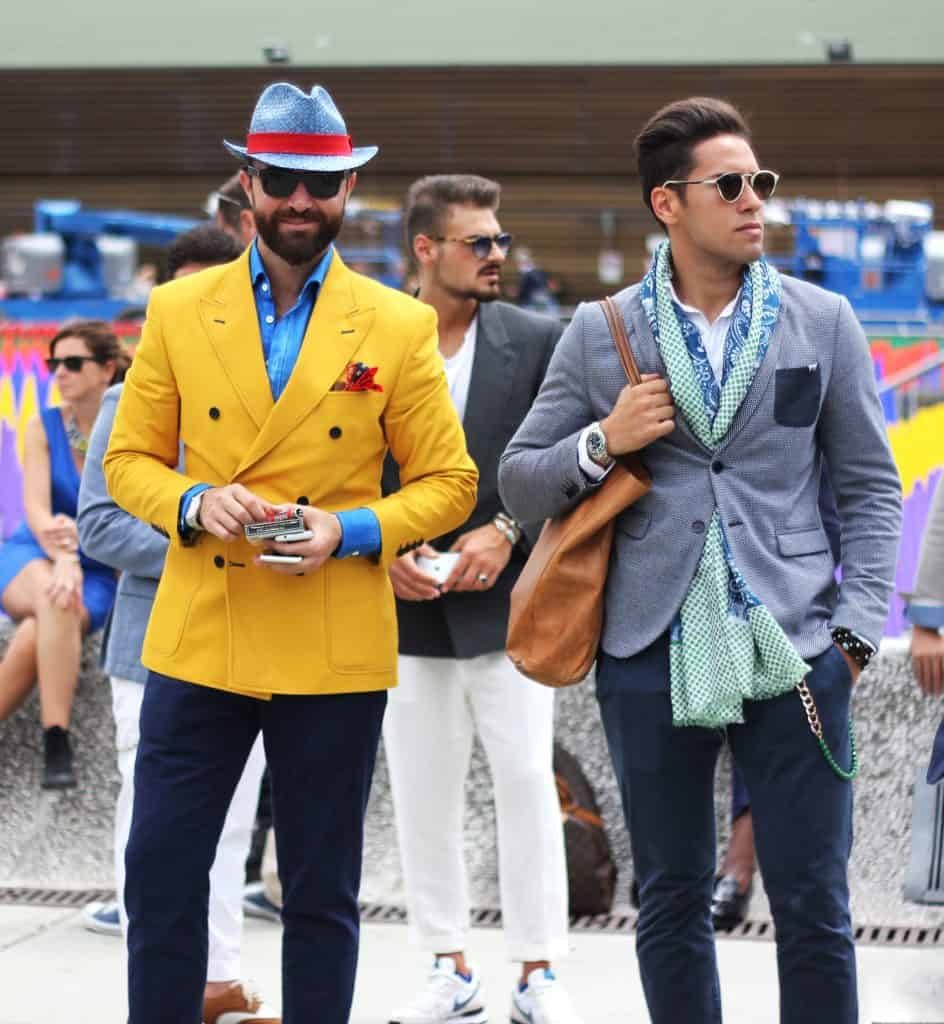 Três homens estão de pé, em ambiente aberto, na rua, sendo dois mais a frente e outro no centro atrás. Os três vestem blazers, cada um de uma cor (um deles chama a atenção pela cor amarela), e óculos escuros.