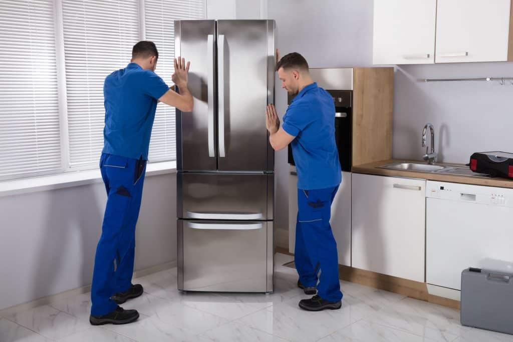 Dois homens vestidos com roupa azul, instalando uma geladeira na cozinha.