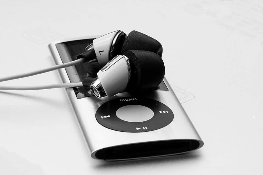 Imagem em preto e branco de um reprodutor MP3 com um fone conectado.