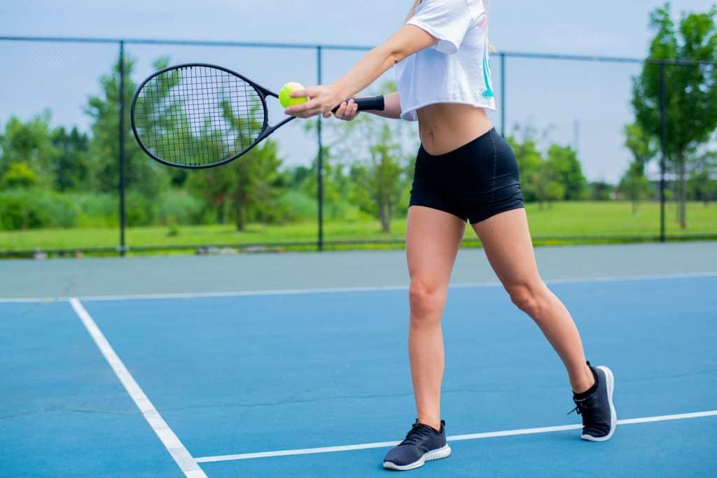 Imagem de uma mulher jogando tênis.