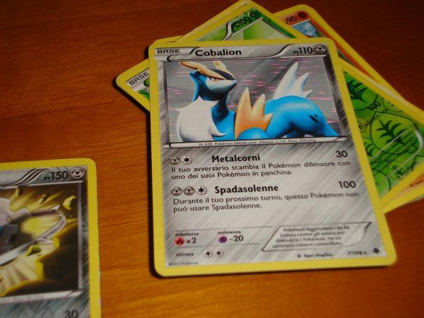 Quatro cartas Pokémon estão sobre uma superfície de madeira.