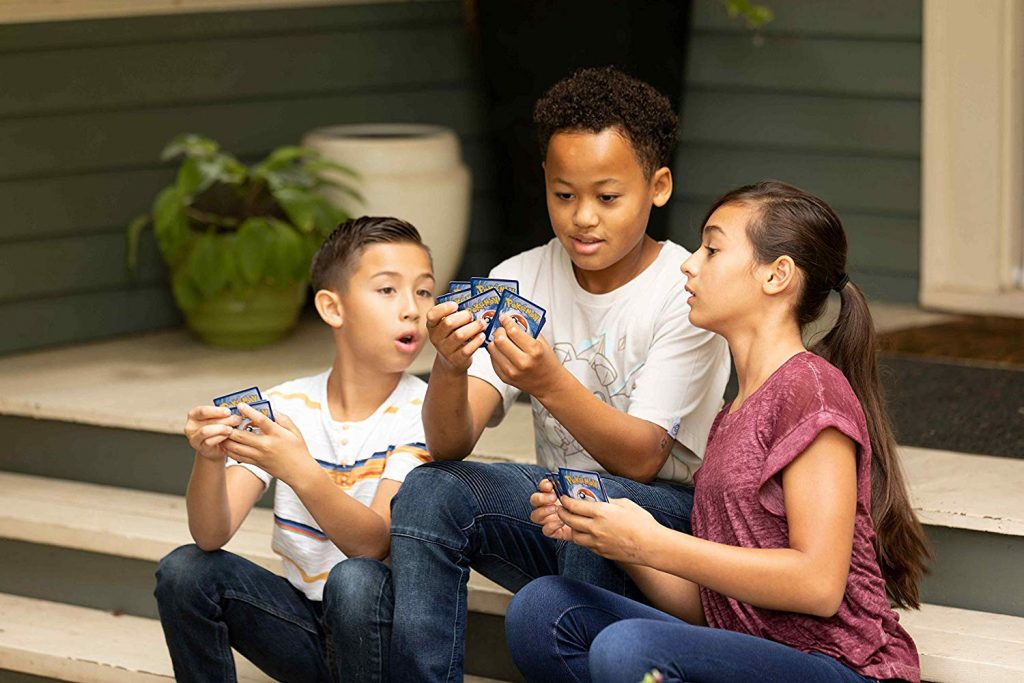Três crianças, uma garota e dois garotos, estão sentados na varanda de uma casa, cada um segurando algumas cartas Pokémon.