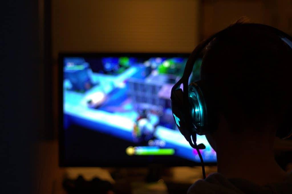 Um garoto de fone joga um jogo no computador.
