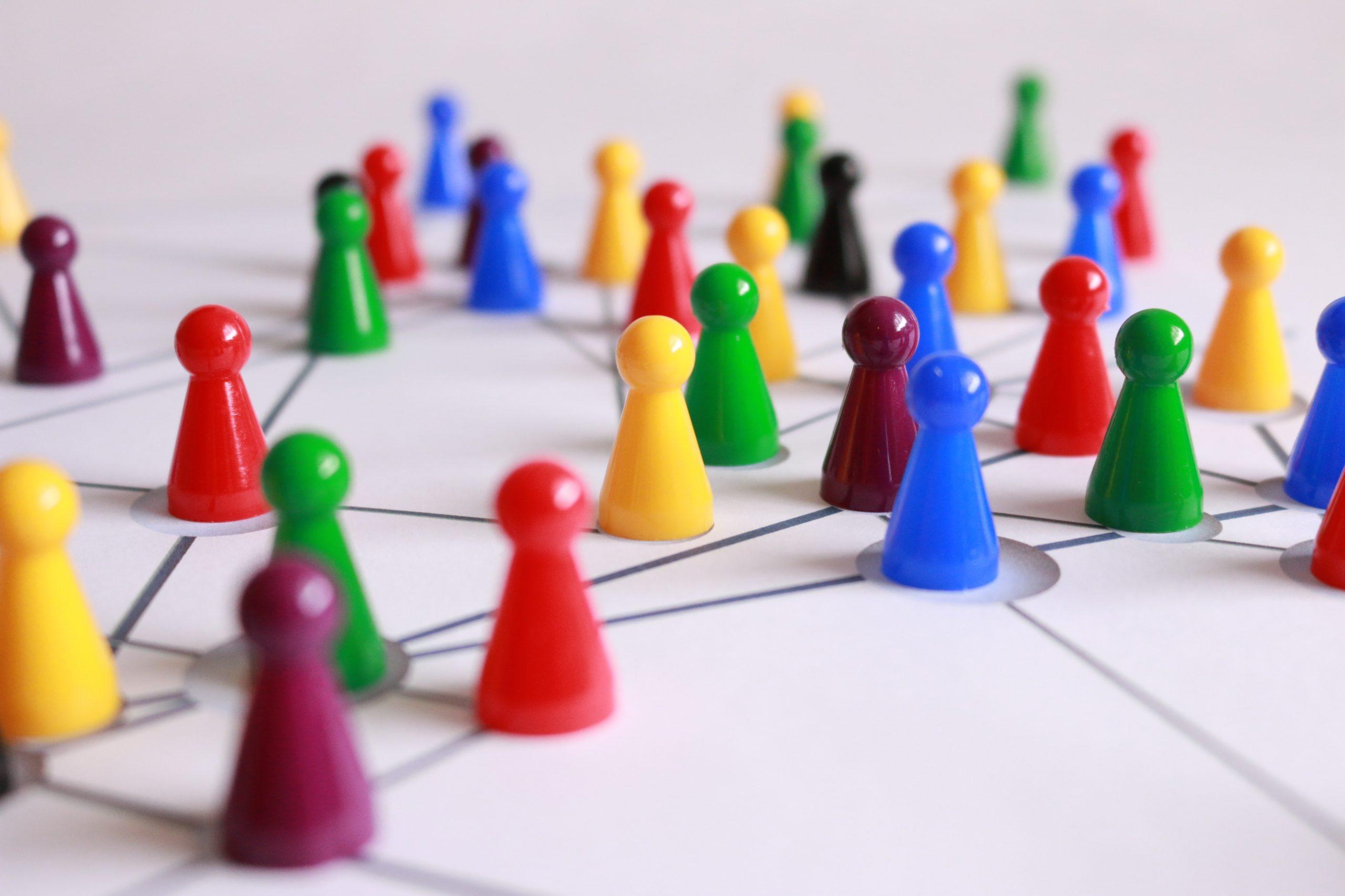 Foto de vários pinos coloridos de jogos de tabuleiro, em cima de o que se assemelha com um tabuleiro.