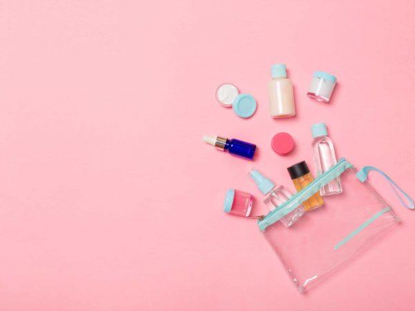 Uma embalagem de kit de viagem está aberto em cima de uma superfície cor de rosa. De dentro da embalagem saem vários itens de cosméticos como potinhos e frascos.