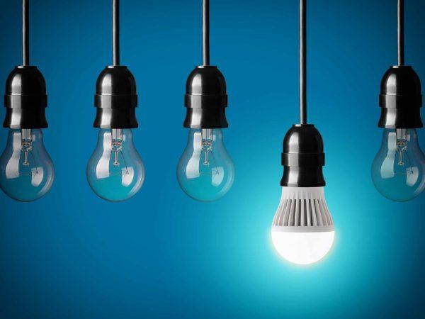 Na foto cinco lâmpadas conectadas a pendentes pretos.