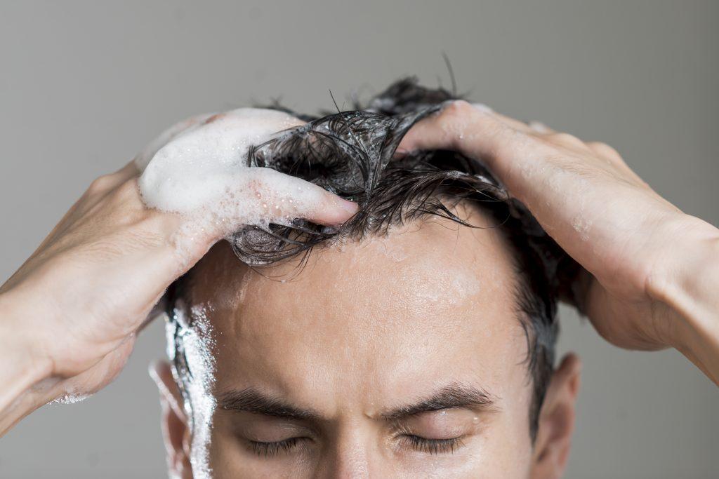 Homem com os cabelos cheio de espuma usando as mãos para massagear o couro cabeludo.