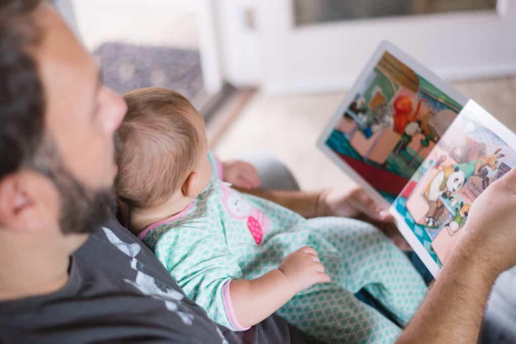 Um homem adulto está sentado enquanto lê um livro infantil em inglês para o bebê que está em seu colo.