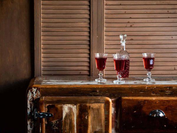 Imagem de licoreira e três taças cheias em cima de um aparador.
