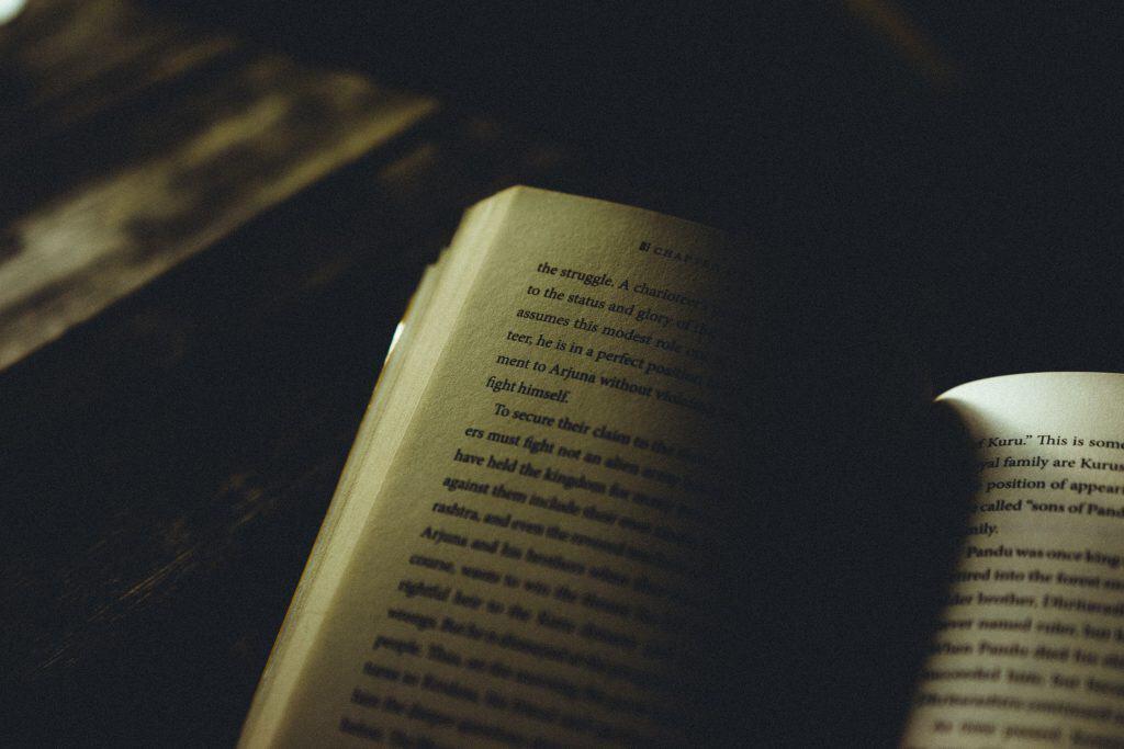 Um livro entreaberto em cima de uma mesa de madeira em um cenário de baixa iluminação.