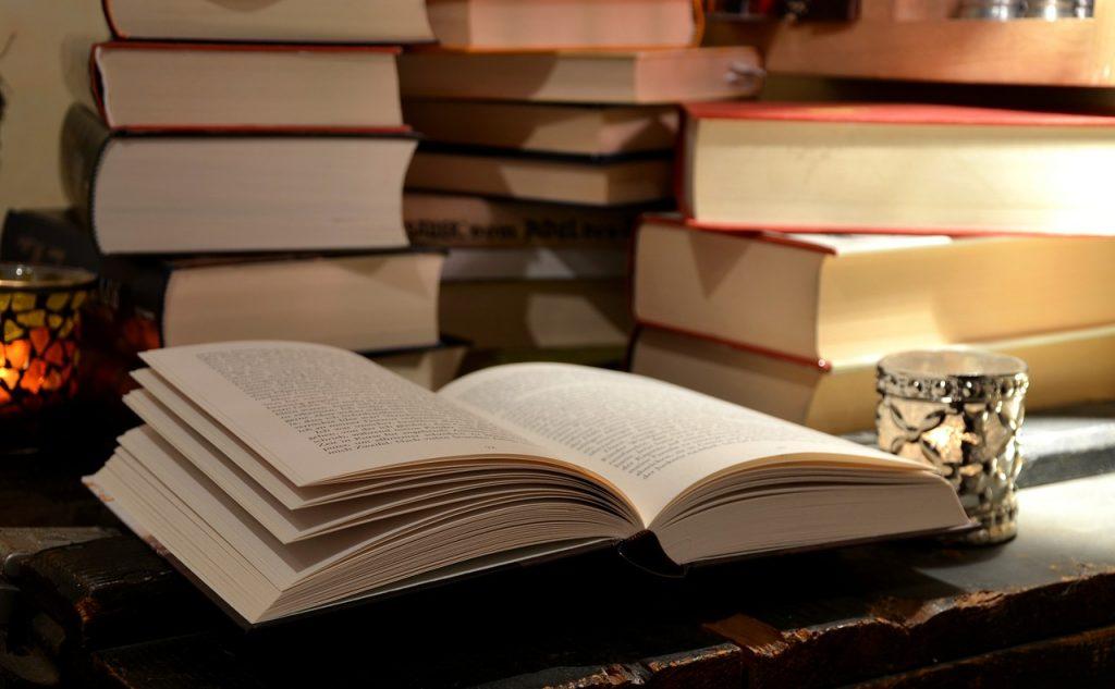 Imagem mostra alguns livros empilhados sobre uma mesa.