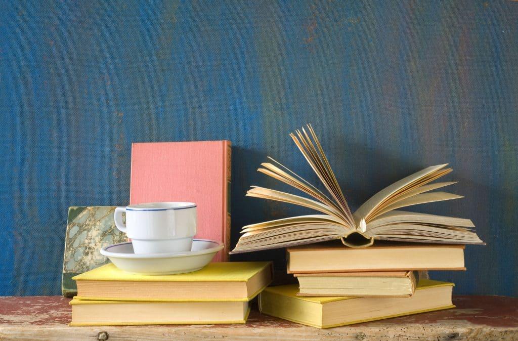 Imagem de livros empilhados e xícara de café.