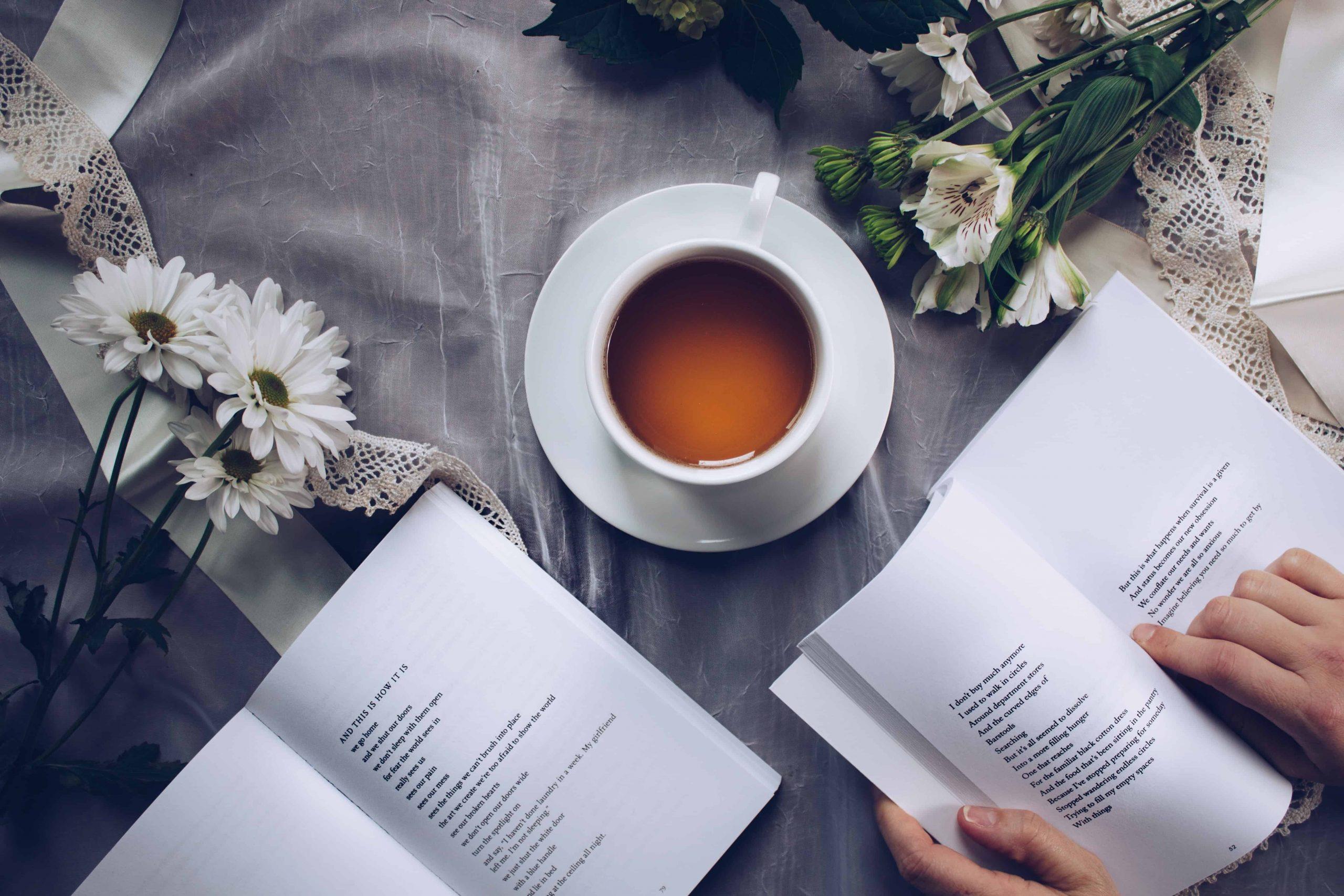 Mãos segurando livro e xícara de café na mesa.