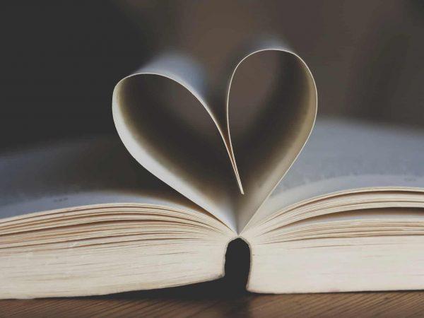 Um livro está aberto em uma mesa enquanto duas páginas formam um coração.