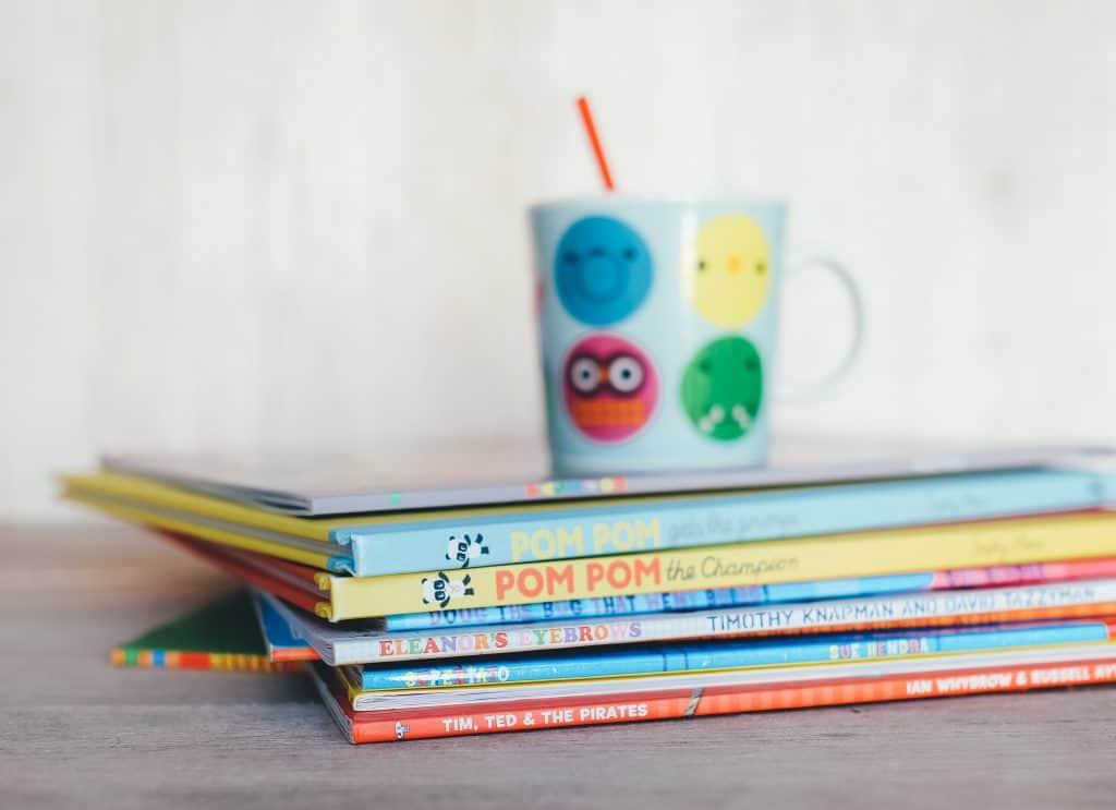 Uma caneca está em cima de uma pilha de nove livros infantis em inglês que encontra-se em cima de uma mesa.