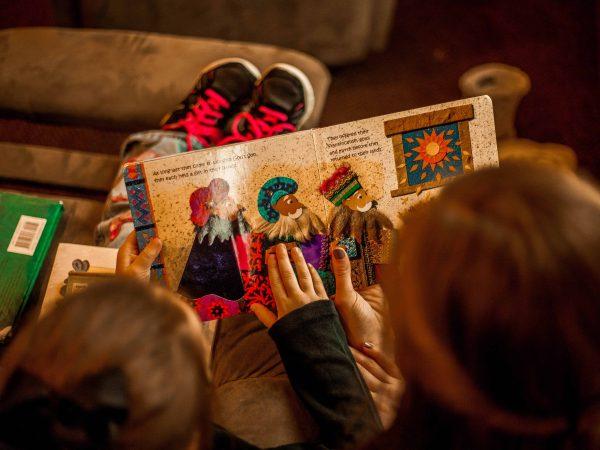 Um mulher adulta e uma menina estão sentadas no sofá enquanto leem a um livro infantil em inglês.