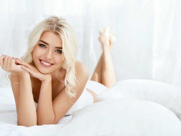 Na foto uma mulher loira deitada em uma cama.
