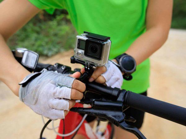 Imagem de um ciclista ajustando uma GoPro ao guidão da bicicleta.