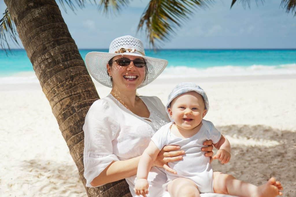 Mãe e bebê vestidos de branco na beira da praia.