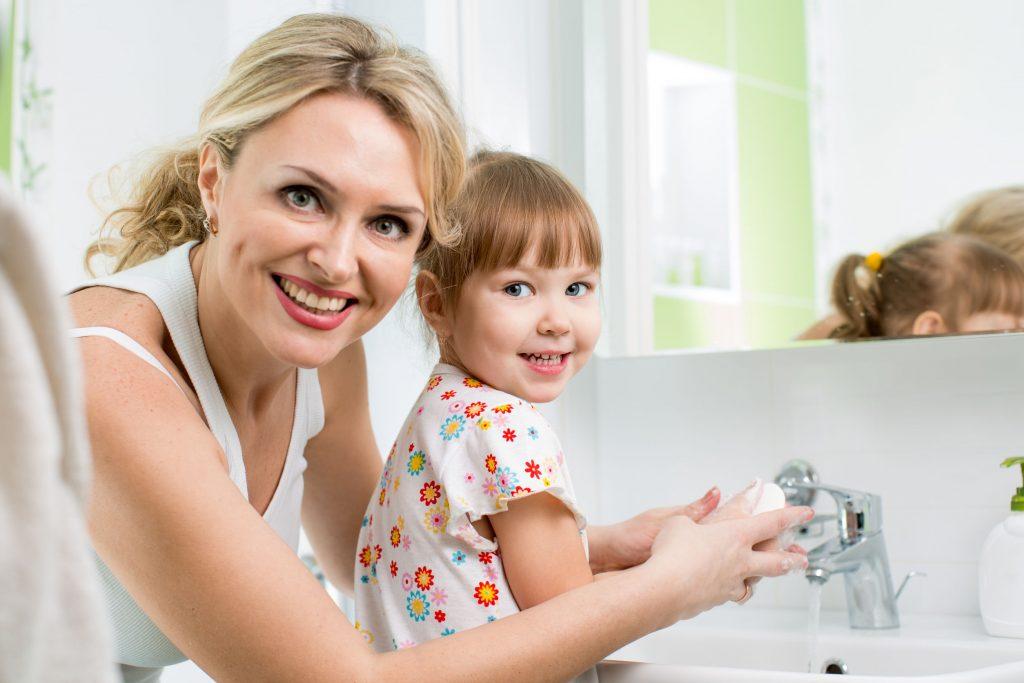 Mãe e filha lavam as mãos com sabonete enquanto sorriem para foto.