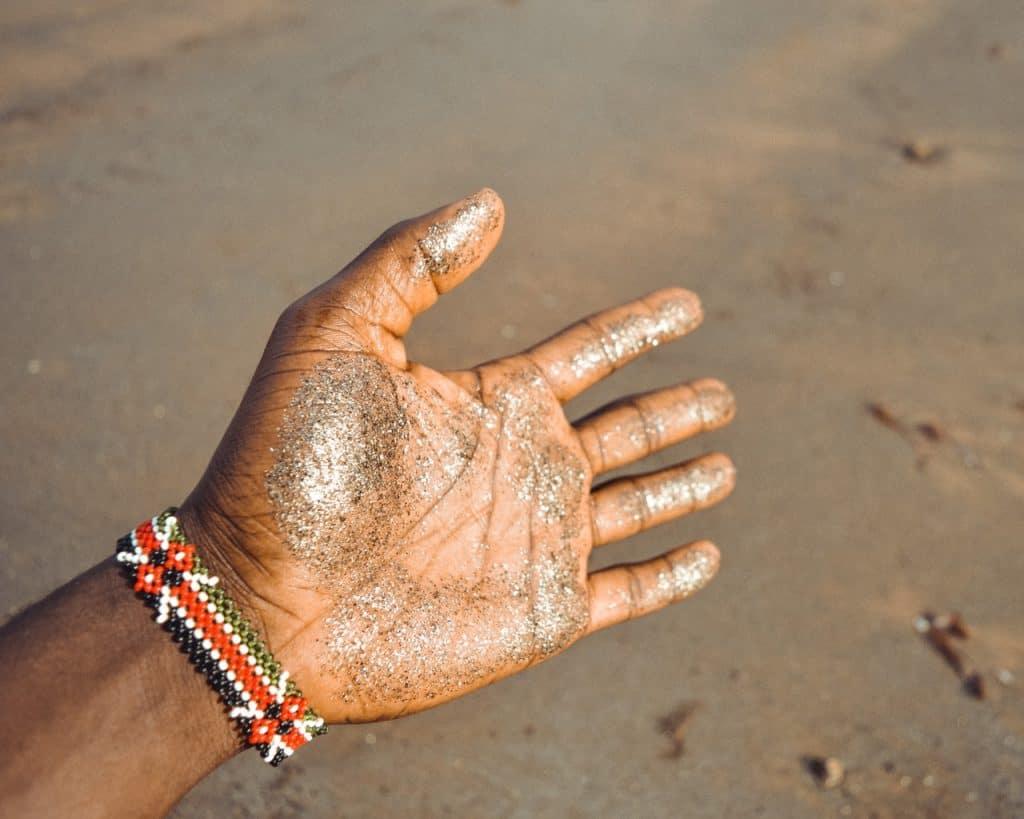 Imagem de mão coberta de glitter biodegradável.