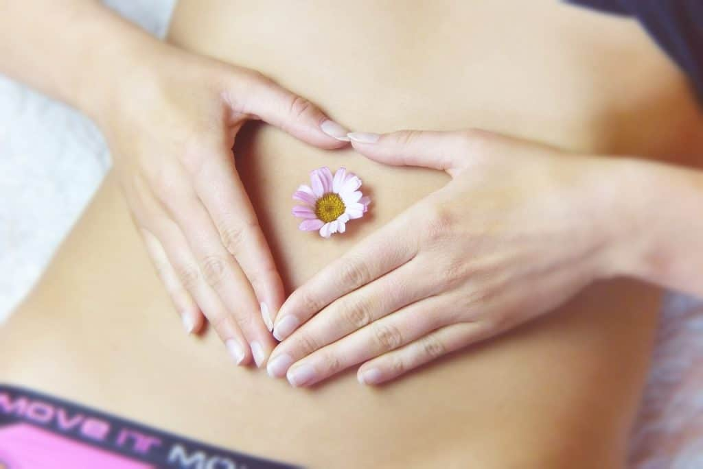 Mulher com mão na barriga e uma flor.