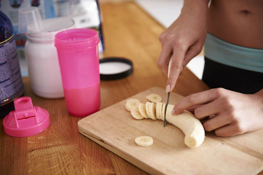 Imagem de uma mulher cortando banana para consumir junto a maltodextrina.