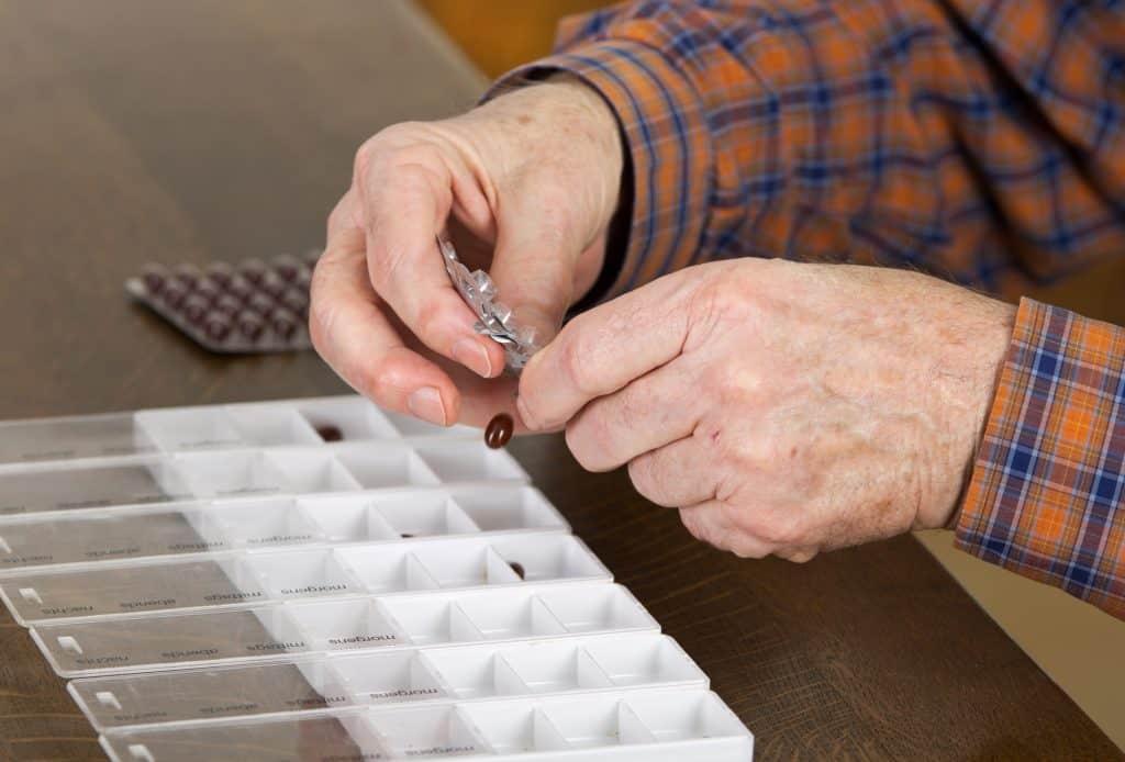 Imagem das mãos de um idoso separando comprimidos.