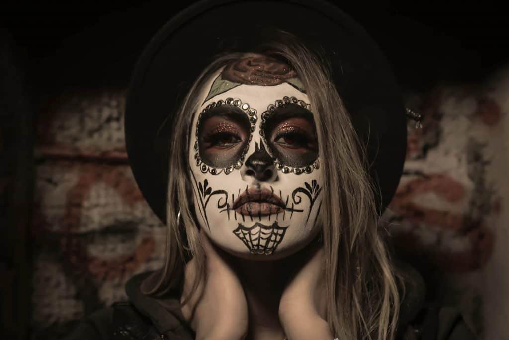 Na foto uma mulher com uma maquiagem de caveira mexicana e chapéu.