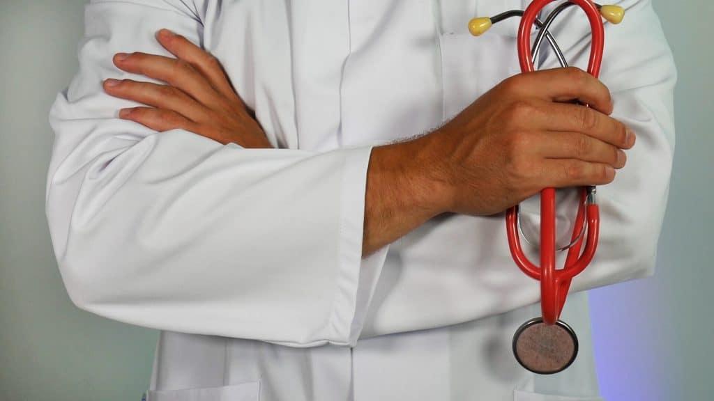 Foto em close, sem aparecer a cabeça, de um médico de jaleco, braços cruzados e segurando um estetoscópio vermelho.