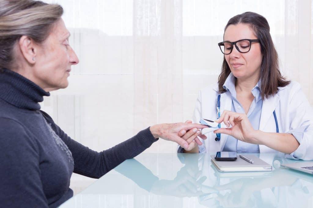 Na foto uma médica colocando um oxímetro de dedo em uma mulher durante uma consulta.