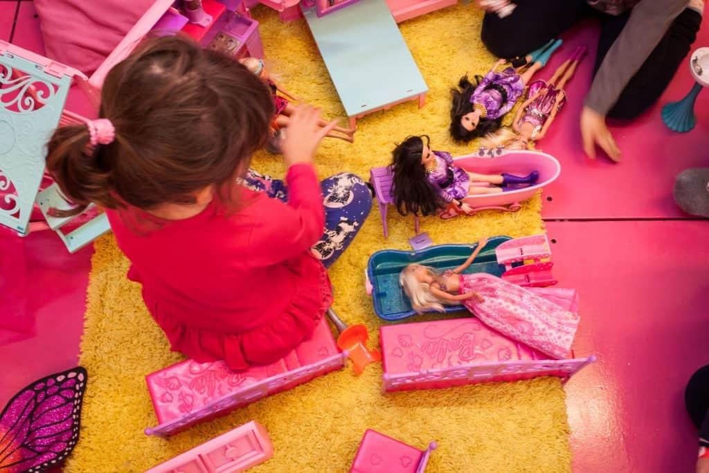 Menina brincando com bonecas barbie.