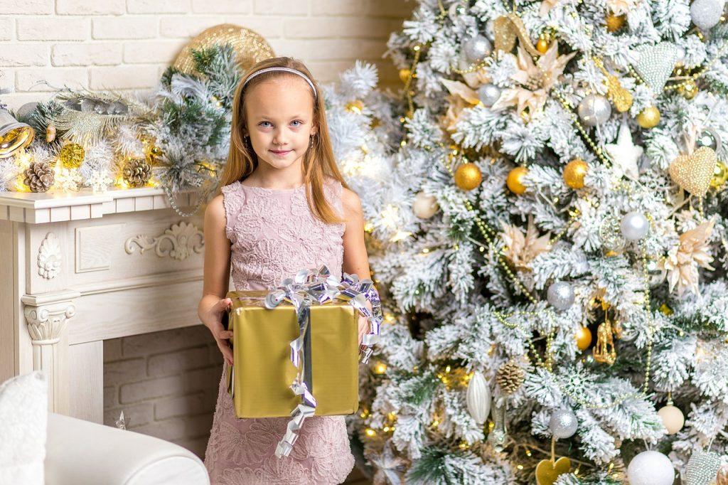 Na foto uma menina segurando um presente ao lado de uma árvore de Natal branca.