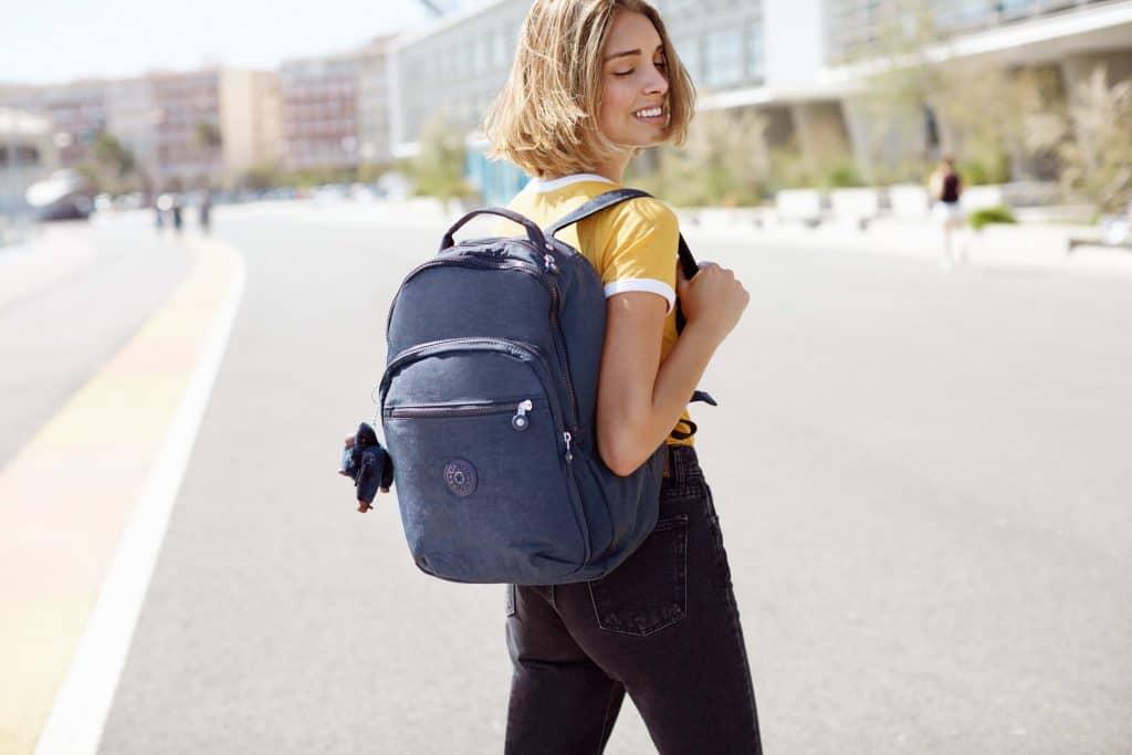 Imagem de uma universitária com uma mochila Kipling.