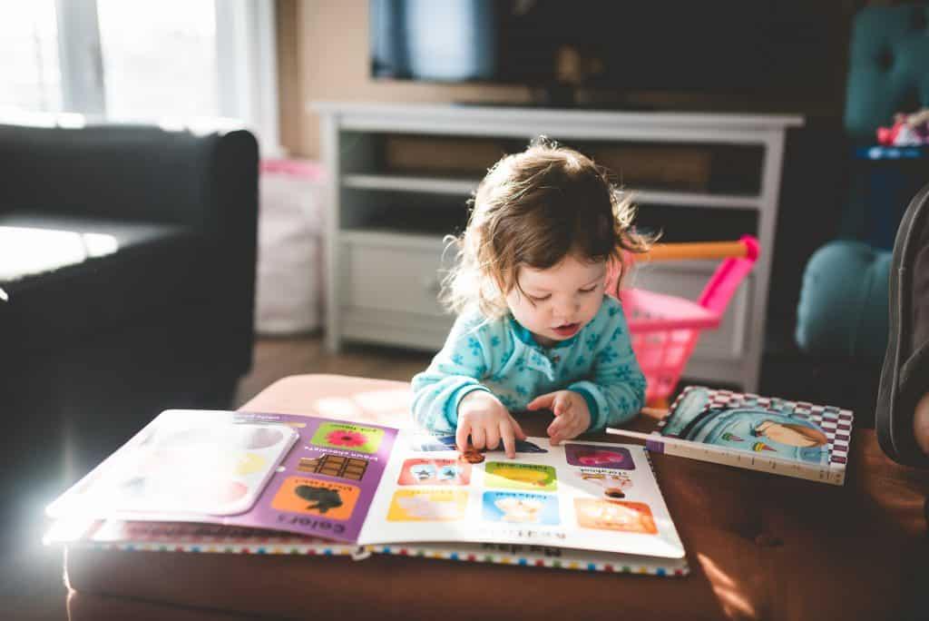Uma criança pequena está numa sala lendo um livro infantil em inglês, que está localizado em cima do sofá.