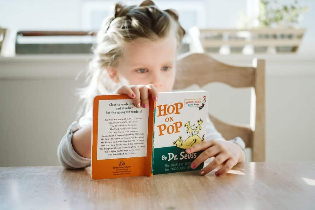 Uma menina está sentada à mesa lendo um livro infantil em inglês.