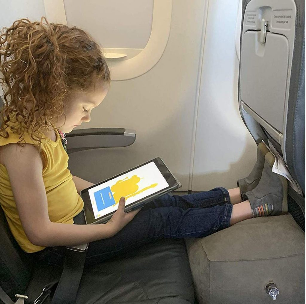 Menina com tablet dentro de avião com os pés sobre um descanso inflável.