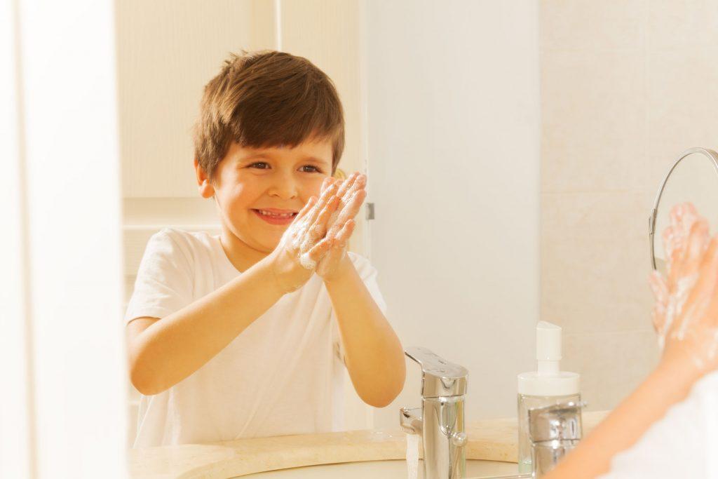 Menino lava as mãos enquanto sorri para espelho.