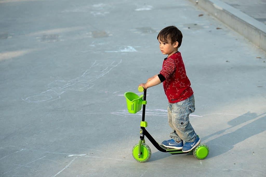 Menino andando de patinete de três rodas.