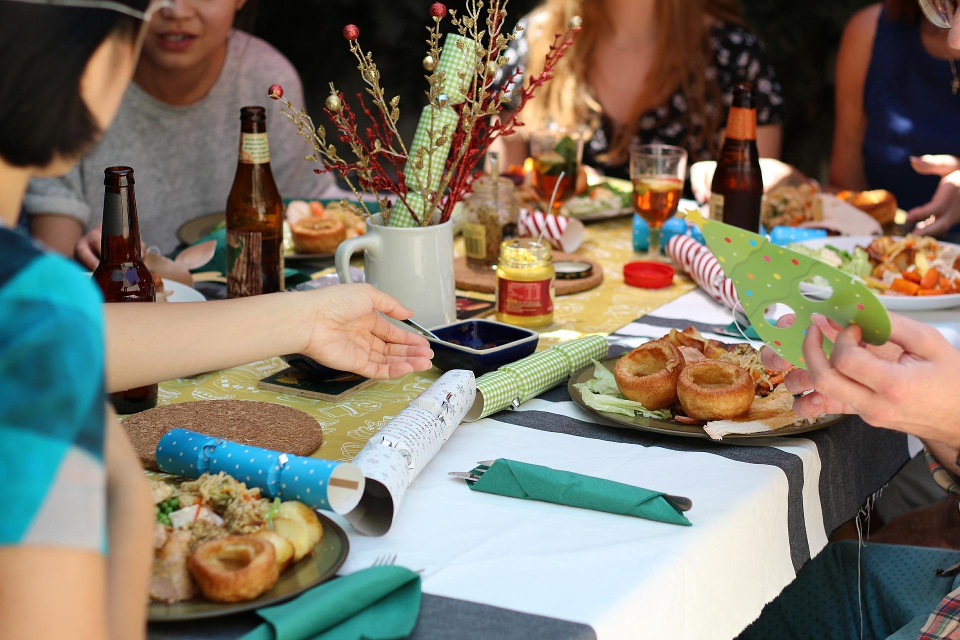 Amigos em volta de uma mesa repleta de comes e bebes, celebrando entre eles.