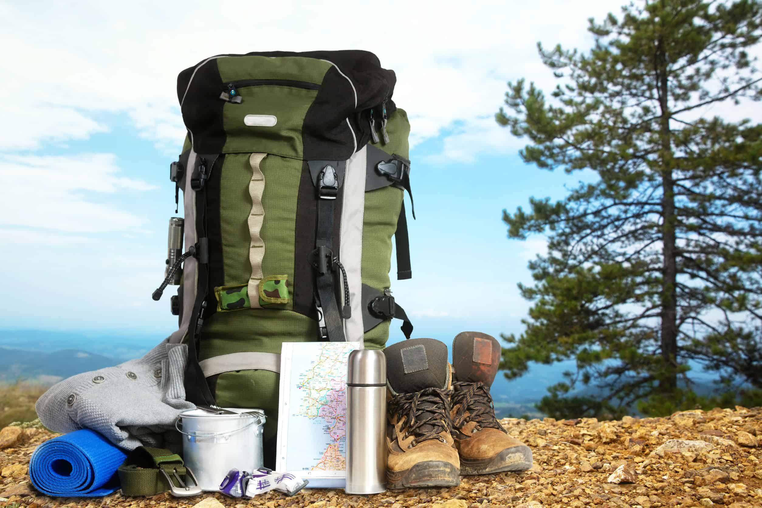 Mochila impermeável com bota, garrafa d'água e toalha ao lado com paisagem ao fundo.