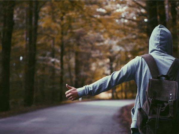 Imagem mostra um homem vestindo moletom e pedindo carona.