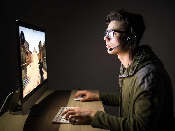 Um adolescente de óculos joga um jogo em um computador.