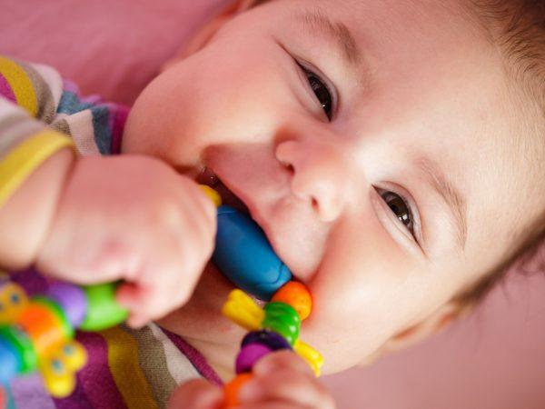 Na foto vê-se um bebê deitado segurando um mordedor colorido.