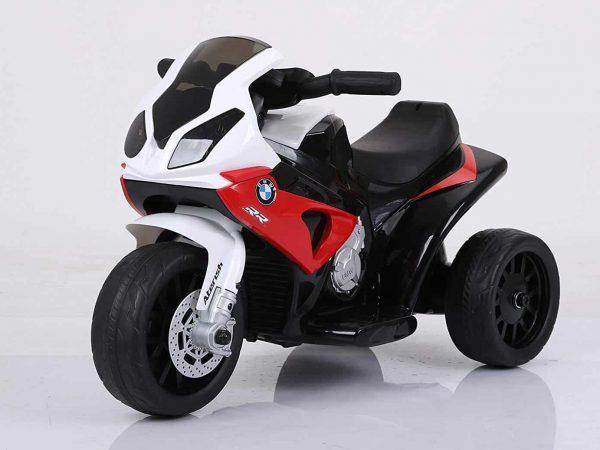 Uma moto infantil elétrica está no centro da imagem em um ambiente todo branco.