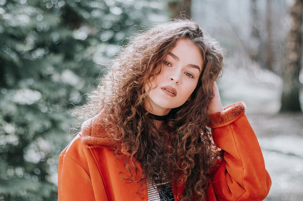 Foto de uma mulher de cabelos cacheados, com uma das mãos no cabelo, expressão facial séria e um casaco alaranjado.