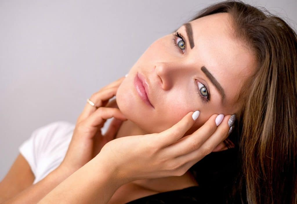 Mulher com mãos na pele do rosto.