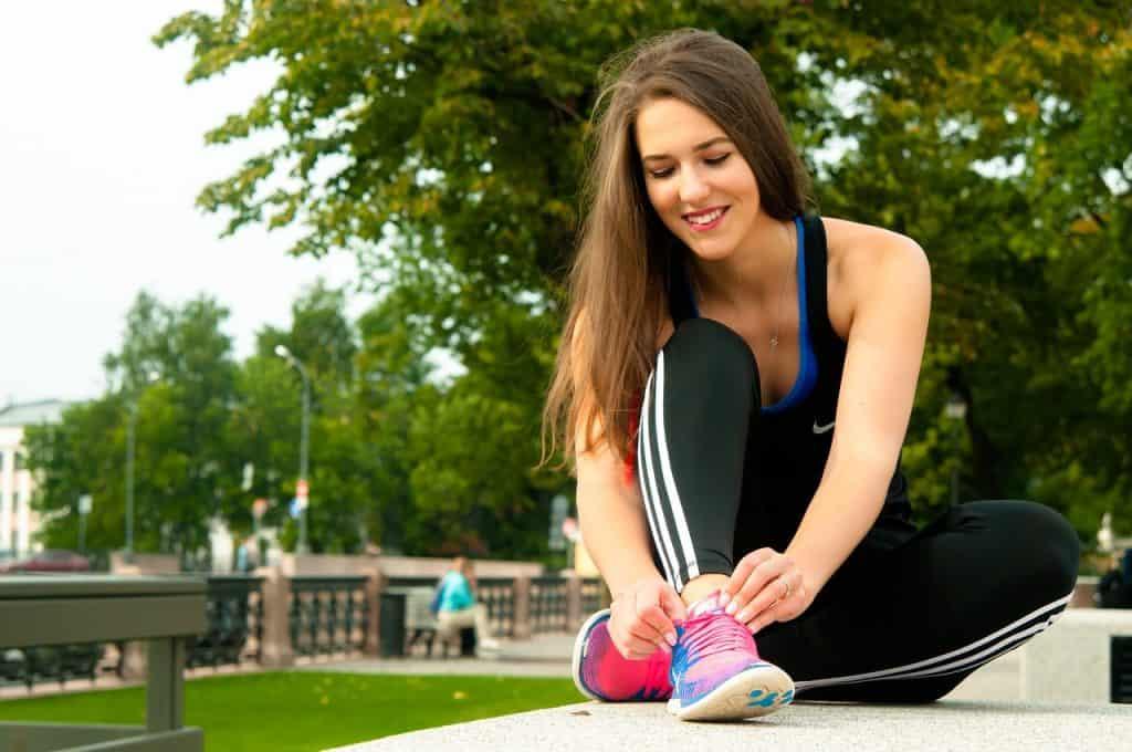 Imagem de uma mulher amarrando o tênis.