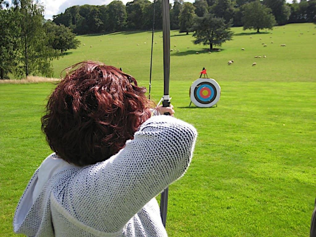 Mulher com arco e flecha mirando em alvo ao ar livre.
