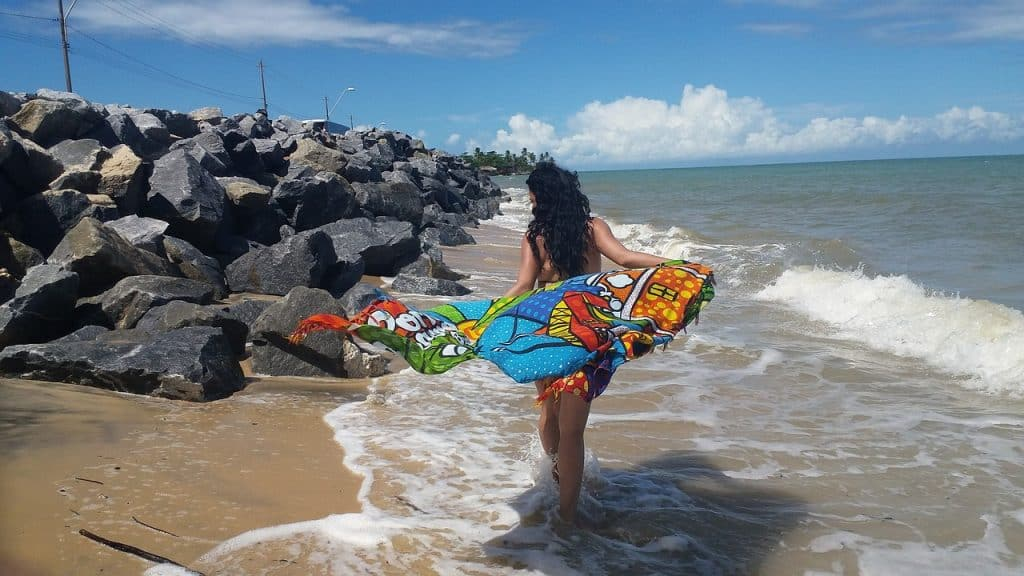 Mulher segurando canga e andando na praia.